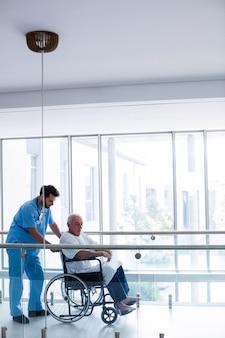 Arts die met mannelijke hogere patiënt in gang in wisselwerking staat