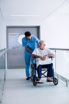 Arts die met mannelijke hogere patiënt op een rolstoel interactie aangaan