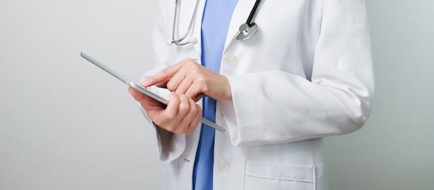 Arts die met moderne digitale tablet en computer voor medische netwerktelecommunicatie werkt om geneeskunde te raadplegen en voor te schrijven.