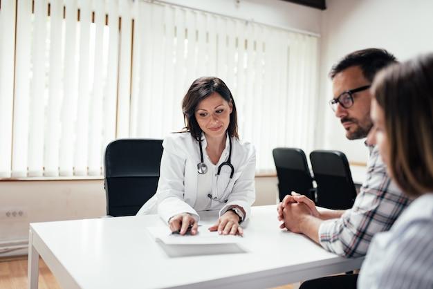 Arts die met paar in de kliniek bespreken.