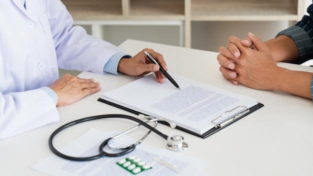 Arts die met patiënt werken die nota's met klembord nemen en iets in zijn medisch bureau, gezondheidszorg en mensenconcept bespreken