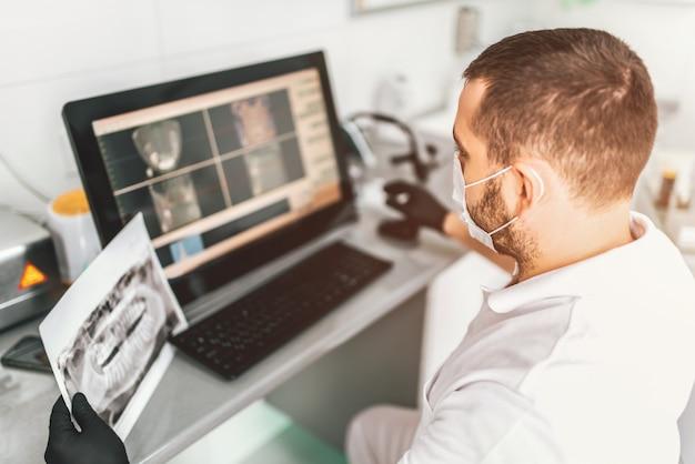 Arts die onderzoek van de röntgenstraal en het kiezen van behandeling in de tandkliniek maakt