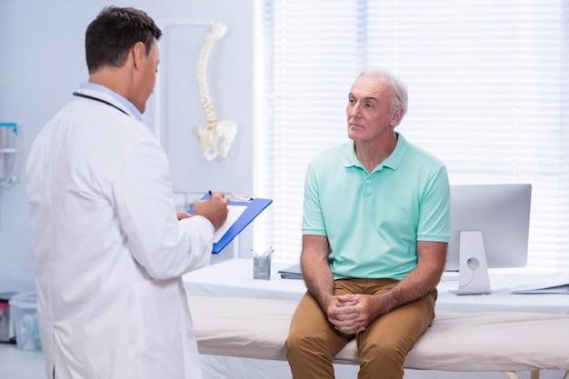 Arts die op klembord in kliniek schrijft