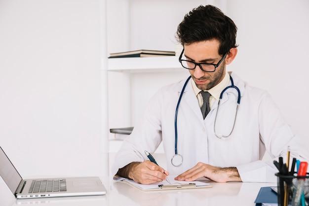 Arts die op klembord met laptop op bureau schrijft