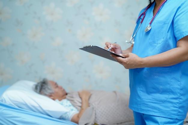 Arts die op klembord schrijft terwijl aziatische hogere vrouw die op bed ligt.