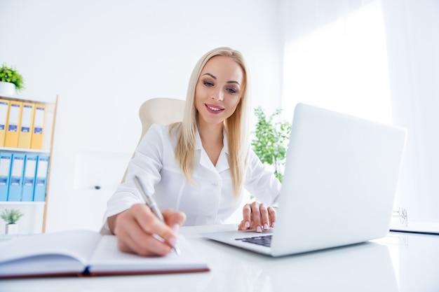 Arts die op laptop in haar kantoor werkt