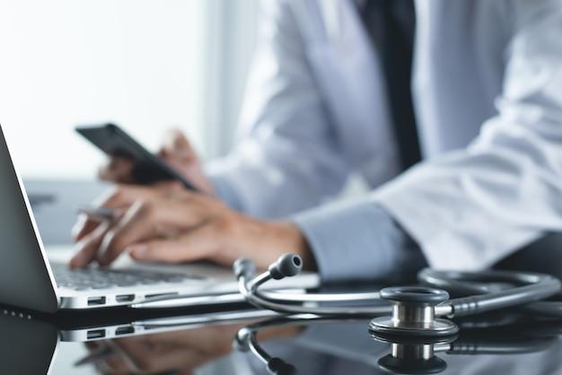 Arts die op laptopcomputer werkt en mobiele telefoon gebruikt in medisch bureau