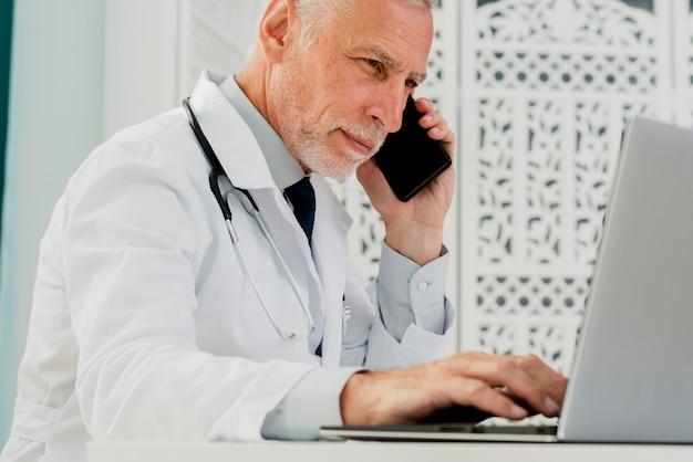 Arts die op zijn telefoon spreekt en laptop met behulp van