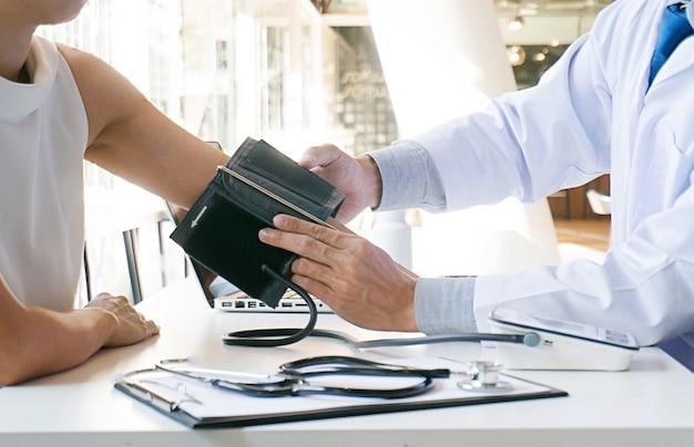 Arts die oude vrouwen geduldige slagaderlijke bloeddruk controleert. gezondheidszorg