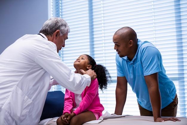 Arts die patiëntenhals onderzoekt