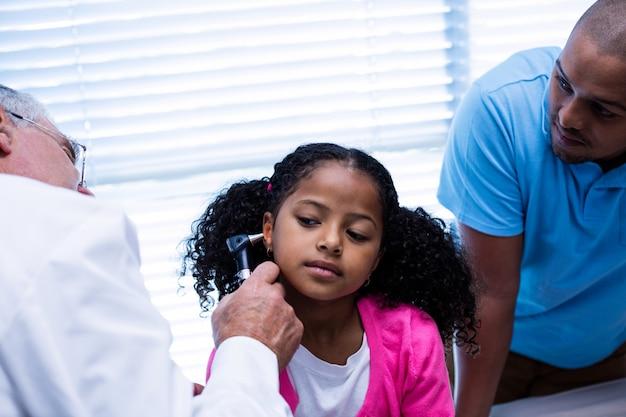 Arts die patiëntenoor met oorspiegel onderzoeken