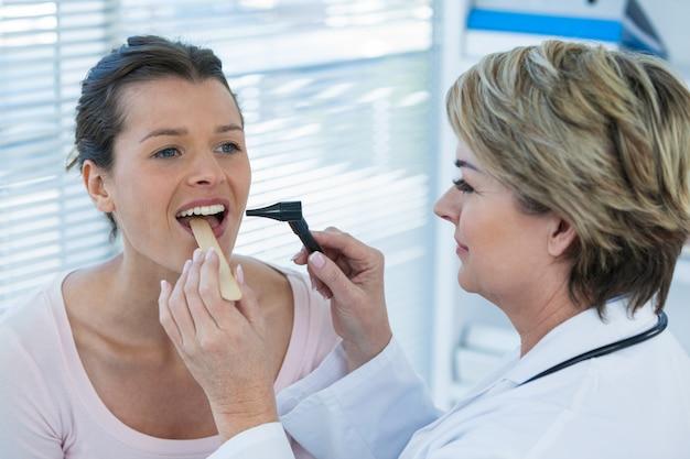 Arts die patiëntentanden met oorspiegel onderzoeken