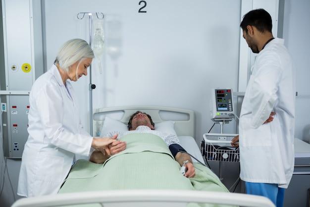 Arts die pols van patiënt controleert