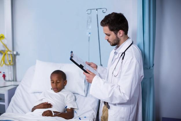 Arts die rapport bekijkt terwijl geduldige slaap op bed