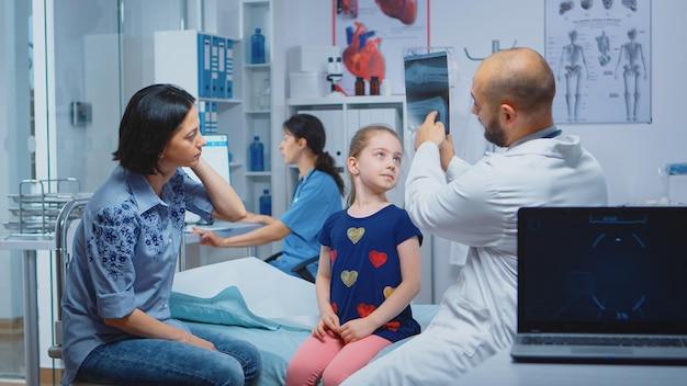 Arts die röntgenfoto van een bot toont aan de patiënt. gezondheidszorgbeoefenaar arts specialist in geneeskunde die consultatie van gezondheidszorgdiensten verleent, radiografische behandeling in het ziekenhuis van de kliniek