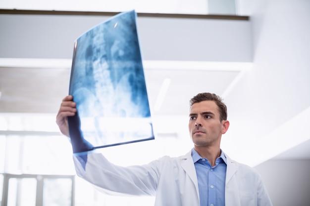 Arts die röntgenstraal van patiënt onderzoekt