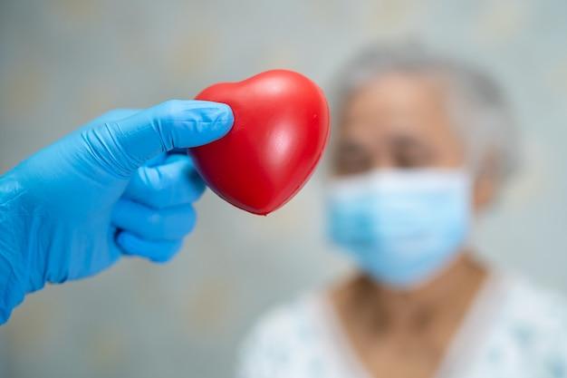 Arts die rood hart met aziatische hogere of oudere oude dame vrouw patiënt houdt die een gezichtsmasker in het ziekenhuis draagt voor bescherming