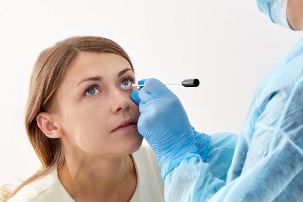Arts die steekproef met wattenstaafje uit het oog neemt
