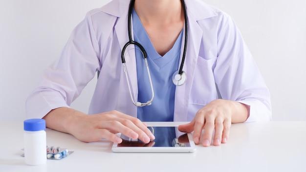 Arts die tablet voor medisch en klinisch online zoeken gebruikt. gezondheidszorg met technologieconcept