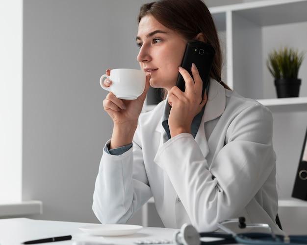 Arts die van een koffiekop geniet