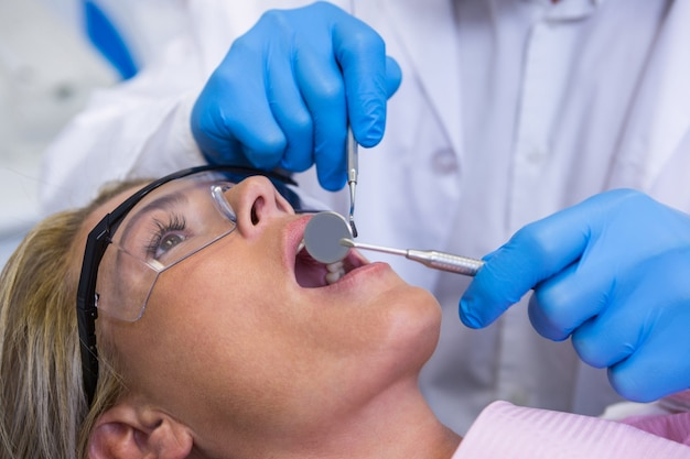 Arts die vrouw onderzoekt bij tandheelkundige kliniek