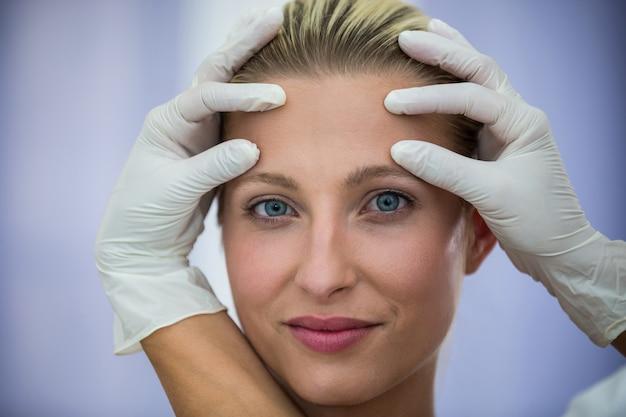 Arts die vrouwelijke patiënten gezicht van kosmetische behandeling onderzoeken