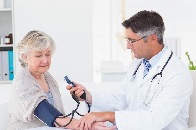 Arts die vrouwelijke patiëntenbloeddruk controleert