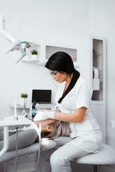 Arts die vrouwentanden in tandheelkundekliniek behandelen. vrouwelijke tandarts in wit uniform en handschoenen met behulp van restauratie-instrumenten.