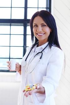 Arts die wit gewaad en de pillen van de stethoscoopholding draagt