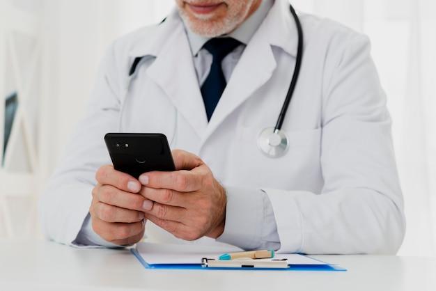 Arts die zijn telefoon gebruikt