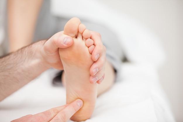 Arts die zijn vingertoppen gebruikt om de bal van een voet aan te raken