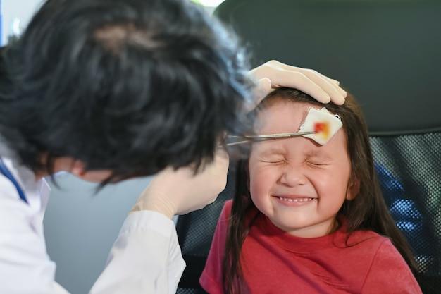 Arts dressing wond op hoofd meisje focus op meisje gezicht wrang gezicht omdat pijn