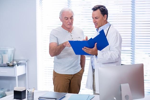Arts en hogere mens die in dossier bespreken