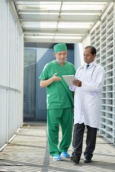Arts en medisch verpleegkundige lopen in de gang van de kliniek en bespreken patiëntengegevens op het scherm van de tabletcomputer