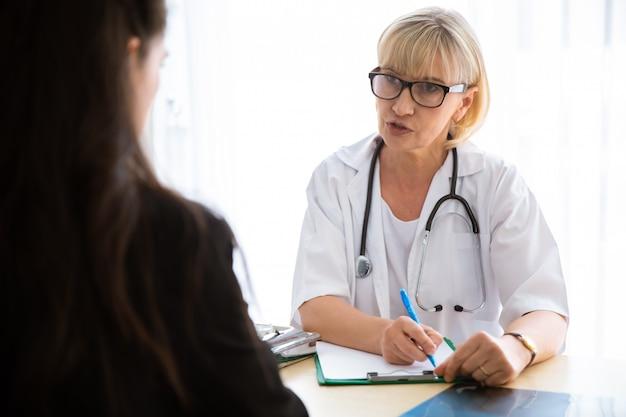 Arts en patiënt bespreken iets zittend aan tafel