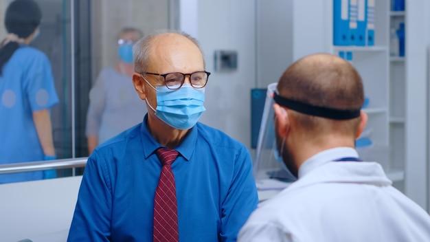 Arts en patiënt bespreken in medisch kantoor tijdens covid-19. moderne privé ziekenhuis of kliniek. overleg met medische arts tijdens de wereldwijde pandemie van covid-19.