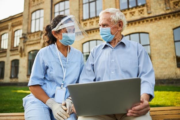 Arts en patiënt die een beschermingsmasker dragen en op een bank zitten met een laptop