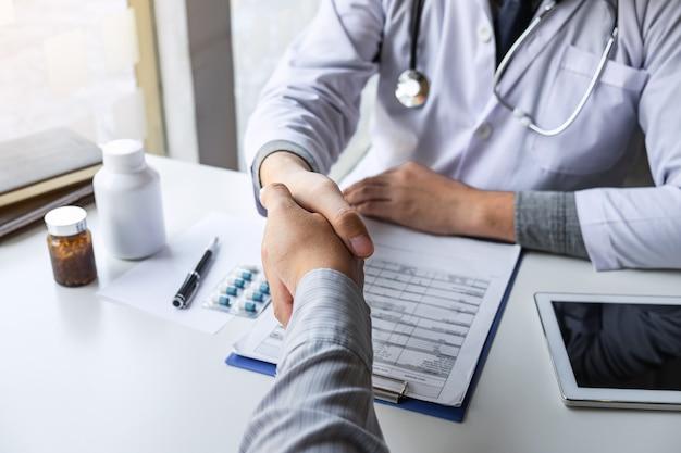 Arts en patiënt handen schudden na een goede en succesvolle behandeling in het ziekenhuis, gezondheidszorg en hulpconcept.