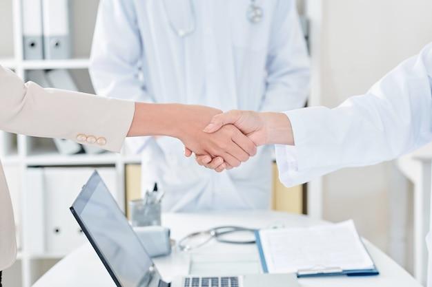 Arts en patiënt handen schudden
