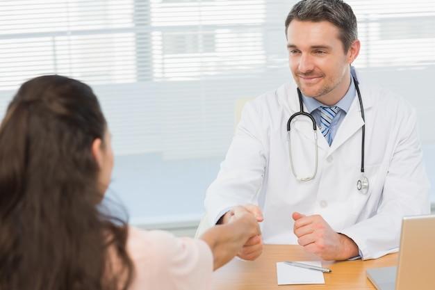 Arts en patiënt schudden handen in medische kantoor