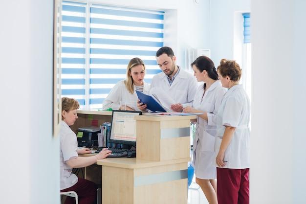 Arts en receptioniste bij de receptie in een ziekenhuis