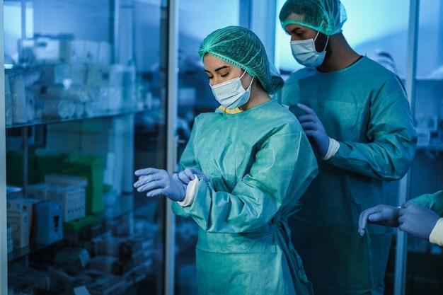 Arts en verpleegkundige bereiden zich voor om in het ziekenhuis te werken voor een chirurgische ingreep tijdens de uitbraak van het coronavirus - focus op het gezicht van de vrouw