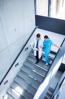 Arts en verpleegkundige bespreken over een rapport tijdens het klimmen naar beneden trappen