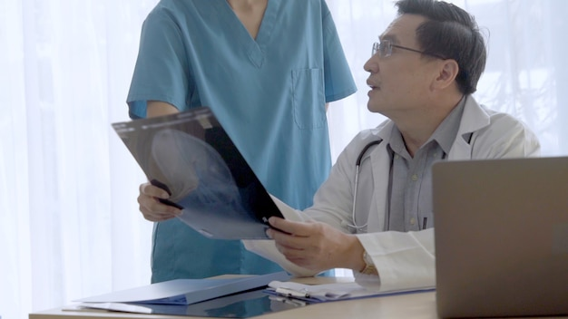 Arts en verpleegkundige bespreken over het resultaat van de operatie dat op röntgenfilmbeeld van het hoofd van de patiënt wordt weergegeven