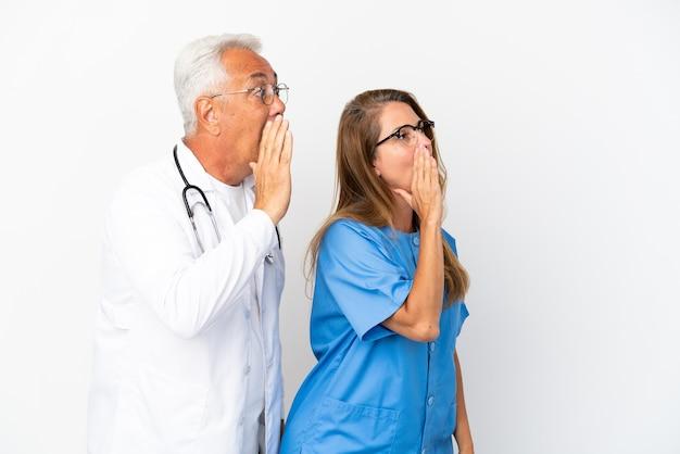 Arts en verpleegkundige van middelbare leeftijd geïsoleerd op een witte achtergrond schreeuwen met de mond wijd open naar de laterale