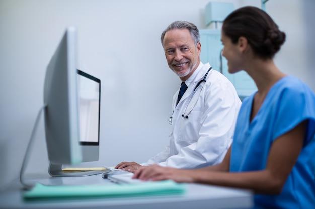 Arts en verpleegster die aan computer werken