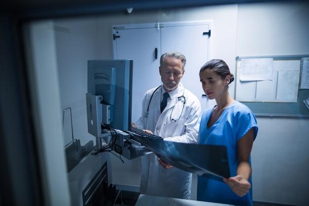 Arts en verpleegster die een röntgenstraal onderzoeken