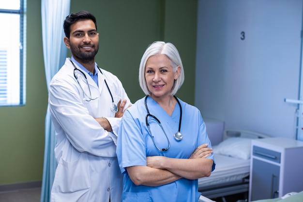 Arts en verpleegster die zich met wapens bevinden die in het ziekenhuis worden gekruist