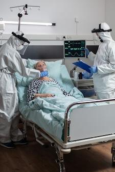 Arts en verpleegster dragen alle pbm-pakken als preventie voor infectie met coronavirus tijdens medische vizit bij senior patiënt, in ziekenhuiskamer die ademt met zuurstofmasker