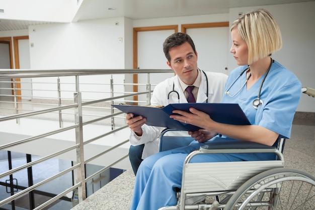 Arts en verpleegster in rolstoel bestuderen map